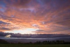 Beau coucher du soleil au-dessus de pré avec Mountain View Image libre de droits