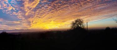 Beau coucher du soleil dans la campagne avec le ciel orange images libres de droits