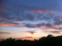 Beau coucher du soleil de rouge et d'or au-dessus de la colline Photo libre de droits