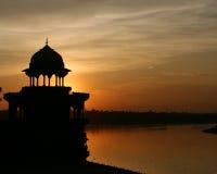 Beau coucher du soleil derrière le temple dans l'Inde avec de l'eau Image stock