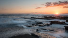 Beau coucher du soleil dramatique au-dessus d'une côte rocheuse Images stock