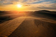 Beau coucher du soleil en dunes de sable au-dessus de désert images libres de droits
