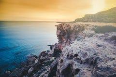 Beau coucher du soleil lumineux renversant par la mer Roches et azur bleus images libres de droits