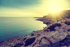 Beau coucher du soleil lumineux renversant par la mer Roches et azur bleus photos libres de droits