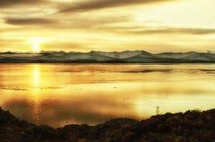 Beau coucher du soleil orange au-dessus du lac avec la montagne Images libres de droits