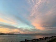 Beau coucher du soleil orange cramoisi sur le bord de mer, vues du soleil du parapet Photo libre de droits