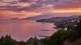 Beau coucher du soleil rose chaud sur la vue criméenne de côte du village belles montagnes sur l'horizon Russie image stock