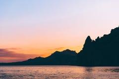 Beau coucher du soleil rouge et pourpre chez la Mer Noire avec la silhouette des roches Karadag, Crimée Photographie stock