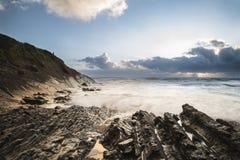 Beau coucher du soleil vibrant coloré au-dessus de plage rocheuse avec le long exp photos libres de droits
