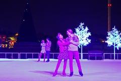 Beau couple patinant sur la glace à l'exposition de Noël dans la région internationale d'entraînement photographie stock libre de droits