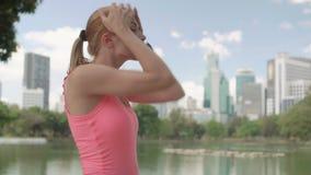 Beau coureur de jeune femme pulsant en parc Formation femelle convenable de forme physique de sport avoir le reste banque de vidéos