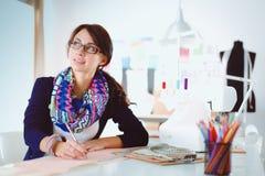 Beau couturier s'asseyant au bureau dans le studio Photographie stock