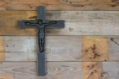 Beau crucifix en bois noir sur le pl en bois naturel minable Photo libre de droits