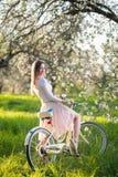 Beau cycliste féminin avec le rétro jardin de bicyclette au printemps Photographie stock
