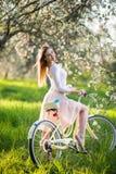 Beau cycliste féminin avec le rétro jardin de bicyclette au printemps Photo stock