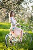 Beau cycliste féminin avec le rétro jardin de bicyclette au printemps Photos stock