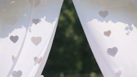 Beau détail de décoration d'arc de mariage avec des coeurs de tissu balançant sur le vent banque de vidéos