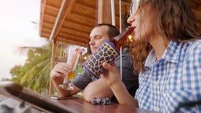 Beau dîner romantique sur les couples de café de plage sur les macédoines de fruits et la bière potables de lune de miel près de  banque de vidéos