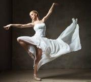 Beau danseur classique dans le costume blanc avec la danse de ondulation de jupe image libre de droits