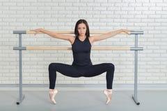 Beau danseur classique pratiquant près du barre au studio de ballet, portrait intégral de ballerine photographie stock