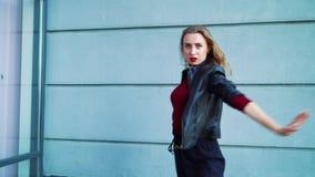 Beau danseur de femme exécutant contre le mur texturisé gris dehors banque de vidéos