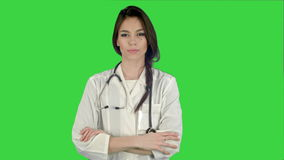 Beau docteur féminin se tenant avec ses bras croisés et inclinant la tête sa tête sur un écran vert, clé de chroma banque de vidéos