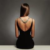 Beau dos de jeune femme dans une robe sexy noire luxe fille s'asseyante de fille de brune de beauté avec un collier sur elle de r Photo stock