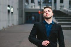 Beau et sérieux homme d'affaires dans un costume posant pour l'appareil-photo sur le fond de l'architecture moderne Photographie stock libre de droits