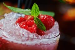 Beau et savoureux cocktail lumineux ou limonade alcoolique avec un chapeau des framboises de glace, en bon état et fraîches surge Photo libre de droits