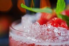 Beau et savoureux cocktail lumineux ou limonade alcoolique avec un chapeau des framboises de glace, en bon état et fraîches surge Photographie stock