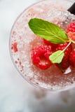 Beau et savoureux cocktail lumineux ou limonade alcoolique avec un chapeau des framboises de glace, en bon état et fraîches surge Photo stock