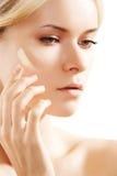 Beau femme appliquant la crème de son de peau sur la joue Images libres de droits