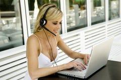 Beau femme avec l'ordinateur portatif et l'écouteur Images stock