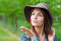 Beau femme avec le baiser de soufflement de chapeau Photos libres de droits
