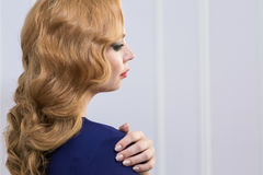 beau femme avec le long cheveu ondulé Coiffure bouclée et maquillage lumineux faits dans les cheveux et le studio de maquillage Photos stock