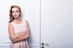 beau femme avec le long cheveu ondulé Coiffure bouclée et maquillage lumineux faits dans les cheveux et le studio de maquillage Images libres de droits