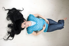 Beau femme avec le long cheveu se trouvant sur l'étage photo stock