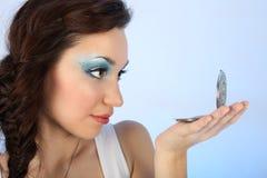 Beau femme avec le renivellement regardant le miroir Photo stock