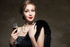 Beau femme avec le vin rouge en verre Rétro type Photographie stock