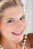 Beau femme avec les dents et les perles blanches Photo stock