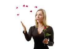 Beau femme avec les pétales de roses rouges Image stock