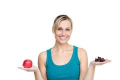 Beau femme comparant la pomme aux chocolats photos libres de droits