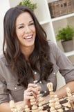 Beau femme de sourire heureux jouant aux échecs Photo libre de droits