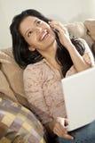 Beau femme latin sur le téléphone portable et l'ordinateur portatif   Photo libre de droits