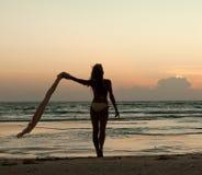 Beau femme restant sur la plage au coucher du soleil Photographie stock libre de droits