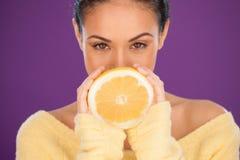 Beau femme retenant une orange divisée en deux Images libres de droits