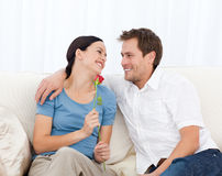Beau femme retenant une rose se reposant sur le sofa Photos libres de droits