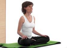 Beau femme s'asseyant sur le couvre-tapis de yoga Photo libre de droits