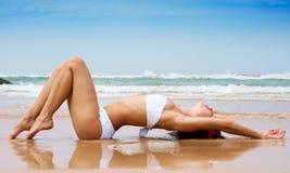Beau femme se trouvant sur le sable humide Photos stock