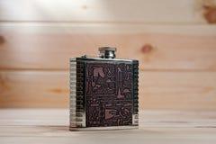 Beau flacon en métal pour les boissons alcoolisées avec des dessins dans le style égyptien sur un fond en bois photo stock